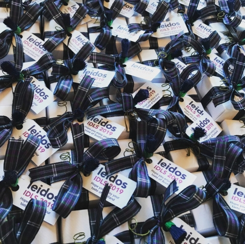 Favour boxes with homemade Scottish Tablet, tartan ribbon, a decorative thistle and corporate logo tag for a conference